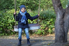 Boy in blue jacket riding on a swing Stock Photography