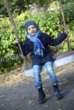 Boy in blue jacket riding on a swing Stock Image