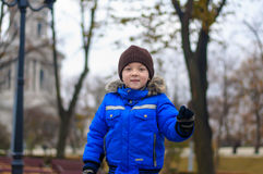 Boy in a blue jacket running in the park Royalty Free Stock Photography