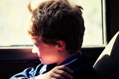 Boy in Blue Jacket Sitting Next to Vehicle Window royalty free stock image