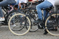 Boy with blue jeans pedal on a black bicycle with many other bik. Es on the street Stock Photos