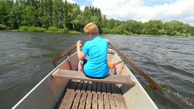 Boy in blue with life jackets at legs floats on vessel boat and hard woarking. Young man in metal  boat sail. On lake water stock footage