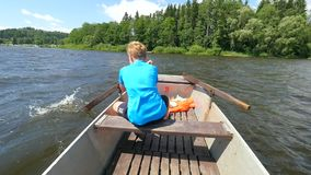 Boy in blue with life jackets at legs floats on vessel boat and hard woarking. Young man in metal  boat sail on lake. Water stock video