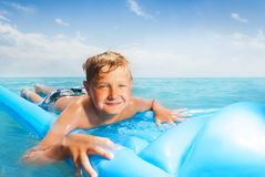 Boy on the blue matrass swim in sea Royalty Free Stock Images