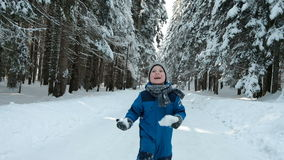 Boy in blue overalls running on road winter forest with snowballs. Baby keeps the snow in his hands obih and quickly steps forward. It is with delight and fun stock video footage