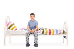 Boy in blue pajamas sitting on a bed. And looking at the camera isolated on white background Royalty Free Stock Photography