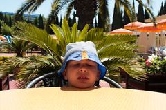 A boy in a blue panama in the heat. Royalty Free Stock Photo