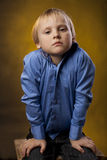 Boy in a blue shirt and black trousers on yellow background Royalty Free Stock Photography