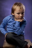 Boy in a blue shirt and black trousers Royalty Free Stock Photography