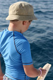 Boy in a blue shirt with a fishing vessel Royalty Free Stock Photo