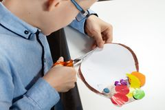 Boy in a blue shirt with mum. The boy`s mom cuts scissors with a plastic work done by a child. royalty free stock images