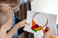 Boy in a blue shirt with mum. The boy`s mom cuts scissors with a plastic work done by a child. stock photography
