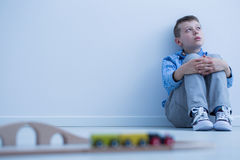 Boy starring at wall. Boy in blue shirt sitting on floor and starring at wall, doesn`t want to play with electric train Royalty Free Stock Images