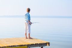 Boy in blue shirt standing on a pie Royalty Free Stock Photo