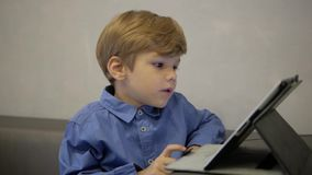 Boy in blue shirt working on tablet.business stock video