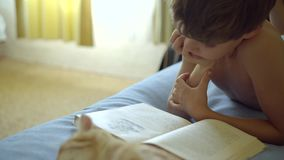 Boy in blue shorts reads a book lying on the bed near a Orange Scottish Fold Cat