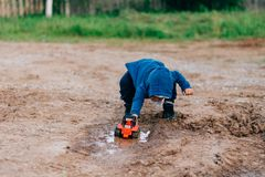The boy in blue suit plays with a toy car in the dirt. The boy in the blue suit covered in mud plays with a toy car in the dirt stock photo