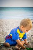 a boy in a blue suit played on the beach Stock Image