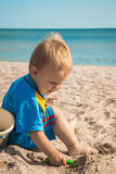 A boy in a blue suit played on the beach Stock Images