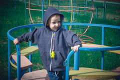 Boy in a blue sweater ride on a swing Royalty Free Stock Images