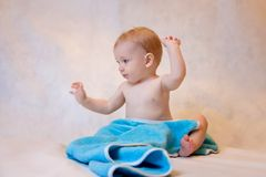 A boy in a blue towel sitting on a light background after a bath. Newborn baby resting in after bath or shower.  stock image