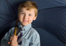 Boy with blue umbrella Stock Images
