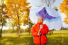Boy with blue umbrella stands under pouring rain Stock Photo