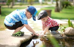 Boy in Blue and White Shirt Playing Near on Body of Water With Boy in Red Shirt Royalty Free Stock Image
