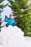 Boy in blue winter jacket throwing snowballs Royalty Free Stock Photography