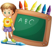A boy beside a board with crayons at the back Stock Photo