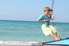 Boy on board of sea catamaran Stock Photos