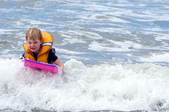 Boy boarding in surf. Learning to surf royalty free stock photos