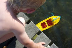 Boy and boat. Little boy playing with his toy boat royalty free stock photography