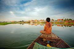 Boy on boat. Cambodian boy on prow of small boat overlooking lake Stock Photography