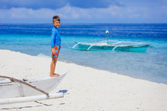 Boy in boat on the beach Stock Image