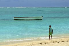 Boy and a boat, Mauritius Royalty Free Stock Images