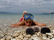 Boy, boat and sea urchins Royalty Free Stock Photography