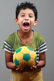 Boy with body smeared with mud holds a football and shows energy Stock Photos