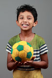 Boy with body smeared with mud holds a football and shows energy Royalty Free Stock Images