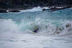 Boy body surfer playing in big Hawaiian Waves Stock Photography