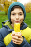 Boy with boiled gold corn. Close up photo of kids mouth and boiled gold corn on the summer green outdoor background Royalty Free Stock Photography