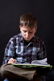 Boy with a book. On a black background Stock Photos