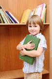 Boy with book against shelf Royalty Free Stock Image