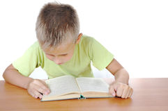 Boy with the book behind a table Royalty Free Stock Photos