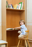 Boy with book before bookcase Royalty Free Stock Image