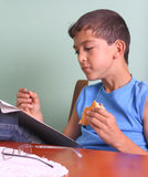 Boy, book and food Stock Photography