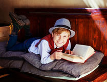 Boy with a book. Happy stylish boy with a book on the bench Royalty Free Stock Image