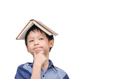 Boy with book on head thinking Royalty Free Stock Photography