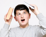 Boy with a book on his head Stock Images