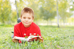 Boy with book laying on grass Royalty Free Stock Photos